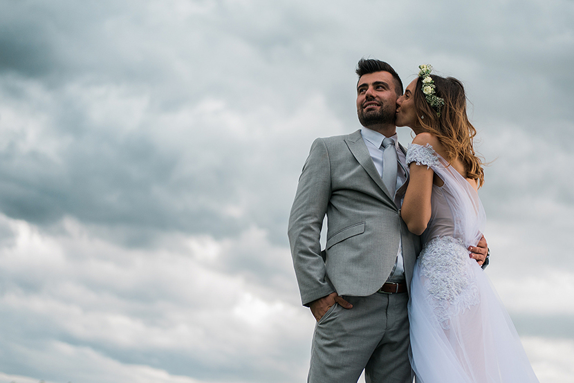 lifestyle esküvői fotográfia, best Hungarian wedding photographer, wedding kiss with clouds in the background, esküvői fotó felhőkkel és viharral